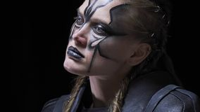 Creepy female alien with long hair and face paint, with white eyes, 4k. Close up of a scary alien woman with white eyes and paint on her face. looking around stock footage