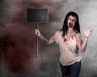 Creepy female zombie holding wooden board Royalty Free Stock Photos
