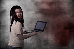 Creepy female zombie typing with laptop Royalty Free Stock Images
