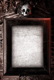 Creepy Frame. Old wooden frame and blank paper hanged on a wall with skull on top Stock Photography