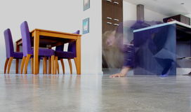 Creepy Girl. Abstract long-exposure photograph taken inside a modern beachouse featuring a blonde girl tumbling from the kitchen royalty free stock photo