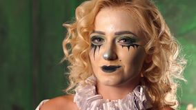Creepy girl with Halloween face chews gum and inflates the bubble. Girl with a makeup for a Halloween party. Close-up portrait, the woman standing in the studio stock footage
