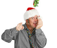 Creepy Guy Checking Breath Under Mistletoe royalty free stock photography