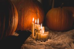 Creepy Halloween candles surrounded by pumpkins royalty free stock photos