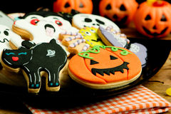 Creepy Halloween cookies and pumpkin baskets filled with candies Stock Image