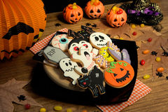 Creepy Halloween cookies and pumpkin baskets filled with candies Royalty Free Stock Images