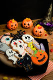 Creepy Halloween cookies and pumpkin baskets filled with candies Stock Photography