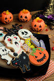 Creepy Halloween cookies and pumpkin baskets filled with candies Stock Images