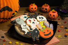 Creepy Halloween cookies and pumpkin baskets filled with candies Stock Photos