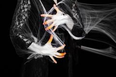 Creepy halloween hand in orange and white with spider web, zombie hand stock images