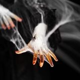 Creepy halloween hands with red, orange and silver covered in a spider web with spiders royalty free stock photography