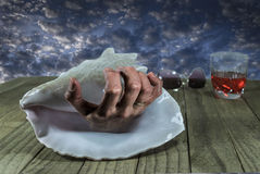 Creepy Hand In Seashell. Scary, crab-like hand in seashell on a dock with drinking glass and sunglasses against a creepy ominous sky Stock Photo