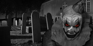 Creepy horror clown in graveyard. Horror clown staring at you in Graveyard a at night Royalty Free Stock Photo