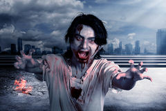 Creepy male zombie in the city Stock Photos