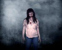 Creepy Male Zombie. Creepy female zombie standing over grunge background Royalty Free Stock Photo