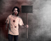 Creepy male zombie holding wooden board. Over grunge background Stock Photo