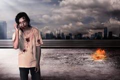 Creepy male zombie talking via cellphone Royalty Free Stock Photo