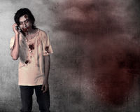 Creepy male zombie talking via cellphone Royalty Free Stock Images