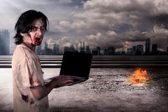 Creepy male zombie typing with laptop. With city on fire background Stock Photography