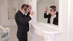 Creepy man with makeup in the form of a skull stands in front of a mirror. Creepy man businessman with makeup in the form of a skull stands in front of a mirror stock video