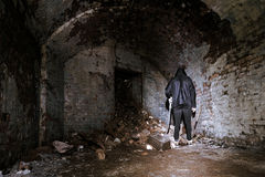 Creepy Man Stands in Derelict Brick Room with Shovel. stock images