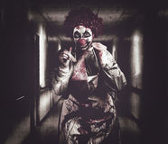 Creepy medical clown in grunge hospital hallway Royalty Free Stock Photography