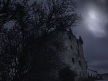 Creepy old tower at night. Creepy medieval tower in an overcast full moon night stock image