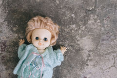 Creepy old doll with eyes open, in a blue knitted costume Royalty Free Stock Image