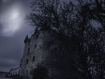 Creepy old tower at night. Creepy medieval tower in an overcast full moon night royalty free stock photography