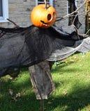 Scary pumpkin head Halloween decoration. Creepy orange molded pumpkin face outdoor decoration Royalty Free Stock Image