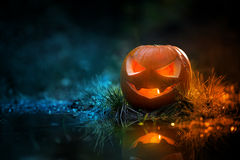 Creepy pumpkin next to a water stream Stock Photo