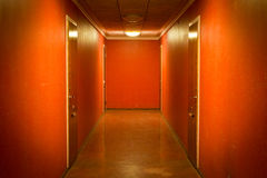 Apartment hallway. Creepy red and brown hallway with four apartment doors Royalty Free Stock Photo