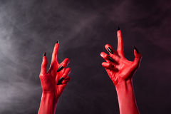 Creepy red devil hands with black sharp nails. Halloween theme stock photo