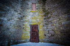 Creepy rusty door in a brick wall. Old rusty door for a guard tower Royalty Free Stock Photo