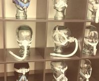 Creepy sepia toned c-pap mask display in medical office. Stock Photos