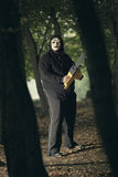 Creepy serial killer with chainsaw. In the woods . Halloween and horror concept stock photo