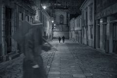 Creepy sinister figure. Old european street from a medieval city by night with a mysterious sinister figure passing by in the foreground stock images