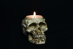 Creepy skull candle on black background - half turn Royalty Free Stock Image