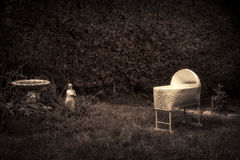Creepy, Spooky Baby Crib. Bizarre, vintage looking photo of a creepy, spooky baby cradle in an overgrown garden Stock Images