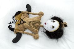 Creepy steampunk doll lying on back with legs tucked. Creepy steampunk rag doll lying on back with legs tucked back. High angle view. Lifesize doll on a grungy Stock Image