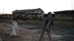 Creepy two zombies in bloody clothes walking through the ruined city during the zombie apocalypse. Abandoned place with
