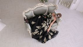 Creepy woman in dress and with makeup in the form of skull lies on a retro sofa. A creepy woman in a medieval dress and with makeup in the form of a skull lies stock video