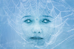 Creepy zombie child face covered in spiderweb Stock Photography