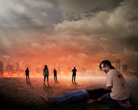 Creepy zombie eat dead man flesh. With city on fire background Royalty Free Stock Image