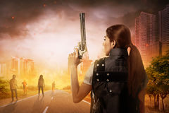 Creepy zombie looking at asian woman holding gun. On forest in the city Stock Image