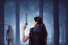 Creepy zombie looking at asian woman holding gun Stock Photography