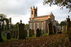 Kirkmabreck Parish Church. Soft sun illuminates the church and grave stones in Creetown, south-west Scotland Stock Image