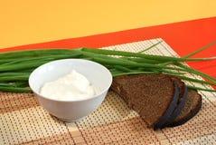 Crema amarga, pan de centeno y cebollas del resorte Fotografía de archivo