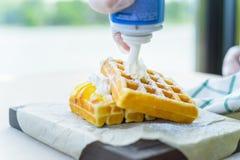 Crema azotada puesta en las galletas belgas fotografía de archivo