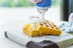 Crema azotada puesta en las galletas belgas imagenes de archivo